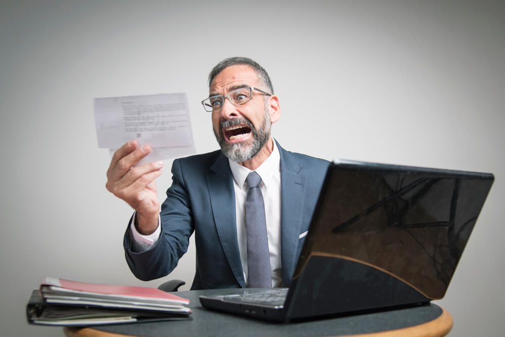 Shocked man holding a tax notice